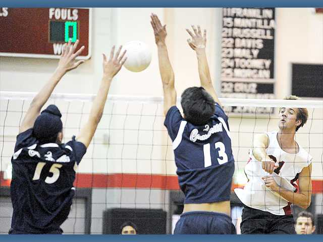 Hart's Tanner Tangberg (21) attempts a kill as Camarillo defenders Satbir Dhaliwal (15) and Evan Yoshimoto (13) try to block Thursday at Hart High.