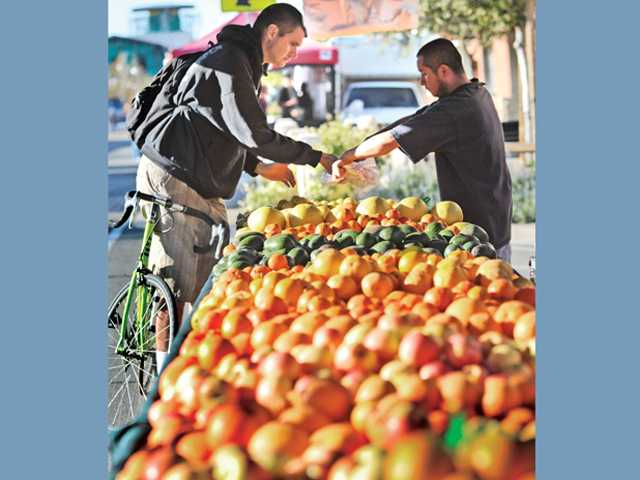 Phillip Lehman, of Newhall, picks out fruit from vendor Manuel Quintana at the Atkins Farms produce stand at the farmers market on Main Street in Newhall on Thursday.