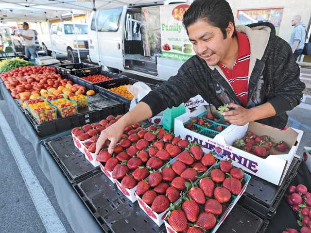 Pedro Aguilar arranges the strawberries at the E&M Family Farms produce stand as he prepares to open for business at the farmers market on Main Street in Newhall on Thursday.