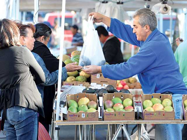 Sami Yordi, center, bags mangos for customers at the Daily Produce stand.