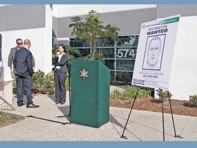 From left, Sgts. William Cotter and Shannon Laren chat with spokeswoman Nicole Nishida, spokeswoman for the Sheriff's Department Homicide Bureau, speak outside the county's Homicide Bureau in Commerce.