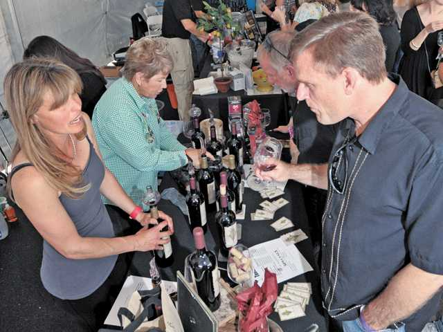 Charlotte Manos, left, of B+E Vineyards pours a selection for James Martin, of Valencia, one of the hundreds of attendees at the Santa Clarita Wine Fest benefiting the Michael Hoefflin Foundation held under tents in the parking lot at Bridgeport Marketplace in Valencia on Saturday.