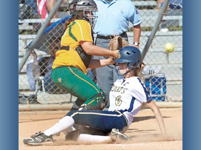 West Ranch's Nikki Klepfer (6) slides safely into home plate, beating the throw to Moorpark catcher Alexa Curt on Saturday at Central Park.