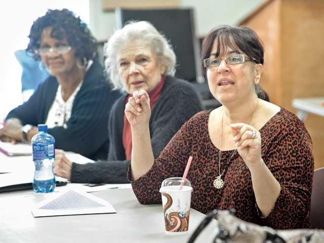 Vernell Adams, left and Jane Hills listen as instructor Judith Cassis, right, leads a  class discussion on haiku poetry at the creative writing class at the SCV Senior Center in Newhall on Tuesday.
