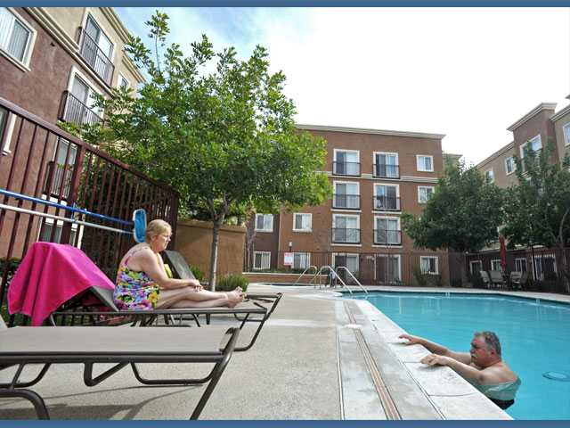 Carol Chapman, 59, left, and Bruce Hines, 65, relax at the pool at the Canyon Country Senior Apartments on Monday.