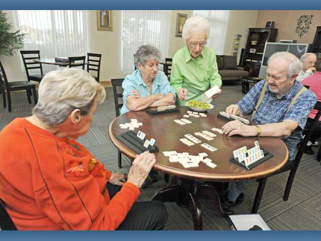 Evelyn Carpenter, second from right, serves up grapes as she and, from left, Lucy Walker, Linda Canham and Robert Canham play Rummikub in the activity room.