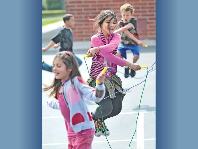 Third-grader Zalekha Babary does a cross-over with her jump rope as she  joins seven classes of third- and fourth-grade students as they participate in the Jump Rope for Heart event at Mitchell Community School in Canyon Country on Tuesday.