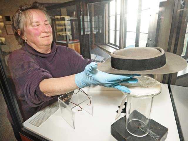 Margi Bertram places Buster Keaton's famous pork pie hat in a display case in the William S. Hart mansion