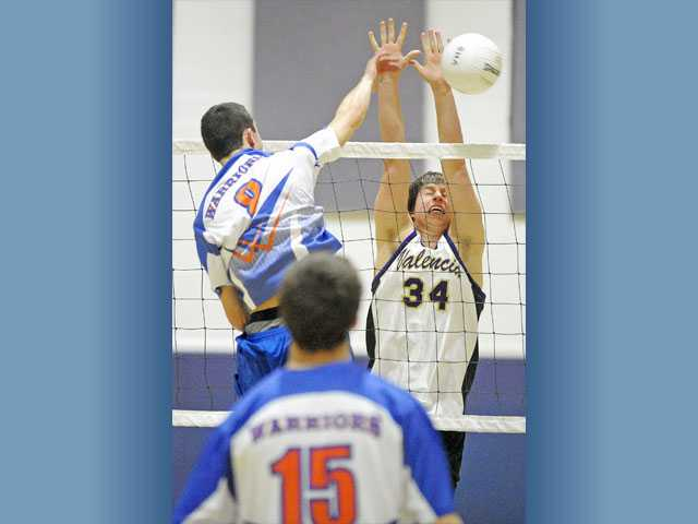 Westlake's Joel Hayes, left, attacks as Valencia middle blocker Daniel Salovich (34) rises to make a block on Wednesday at Valencia High.