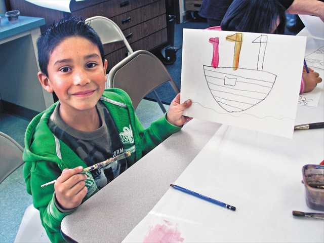 A young CalArts Community Arts Partnership student proudly shows the art piece he made in the after-school Art Pilots Program at Newhall Elementary School.  The program is taught by CalArts School of Art Associate Dean Darcy Huebler along with 16 CalArts students.