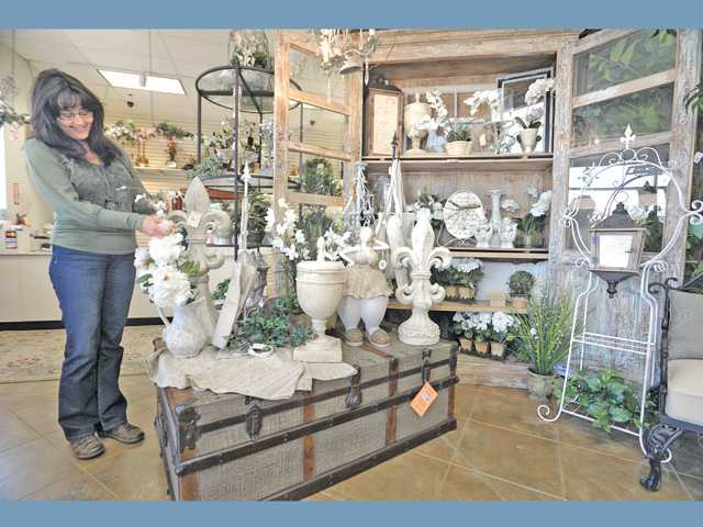 The Decor Store manager Carolyn McLintock arranges the French laundry section of The Decor Store.
