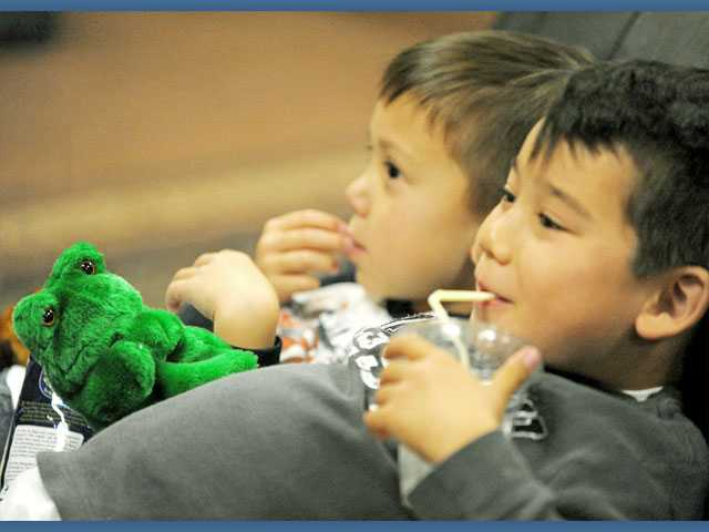 Nathan Egami, 7, right, holds a frog puppet and he and brother Henry, 5, enjoy snacks and stories during Storytime in the Undergrounds coffee shop at Real Life Chuch in Valencia on Tuesday.
