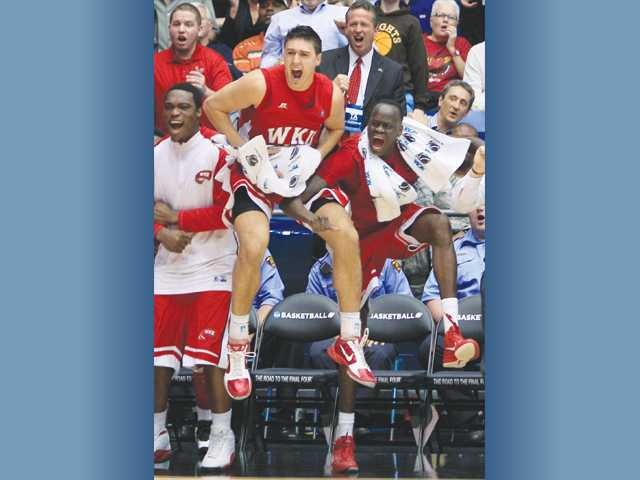 Western Kentucky forwards Vinny Zollo, center, and Teeng Akol leap with joy as the Hilltoppers take the lead against Mississippi Valley State in the second half of the first game of the NCAA Tournament on Tuesday in Dayton, Ohio.