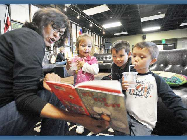 "From left, Liz Wiefferink reads ""Hi! Fly Guy"" by Tedd Arnold to siblings Annalise, 2, Nathan, 7, and Henry Egami, 5, during Storytime in the Undergrounds coffee house at Real Life Church in Valencia on Tuesday."