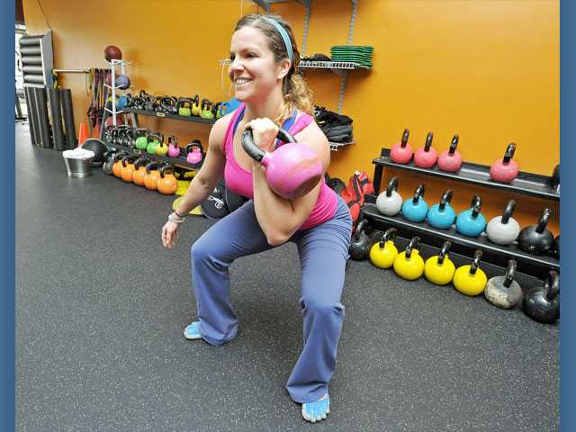 Hold one dumbbell to perform an offset squat exercise.