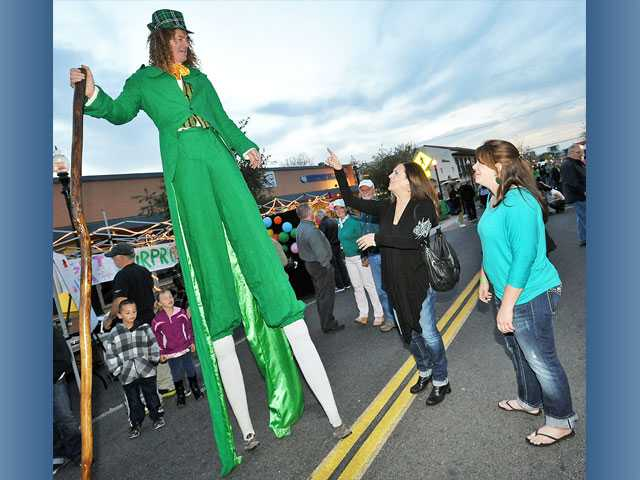 "From left, Rusty O'Flattery, the ""world's tallest leprechaun,"" spends a moment with Patti Sammeter, of Saugus, and daughter Jessica Sammeter, of Agua Dulce, as he entertains the crowd at the St. Patrick's Day-themed Senses block party on Main Street in Newhall on Thursday."
