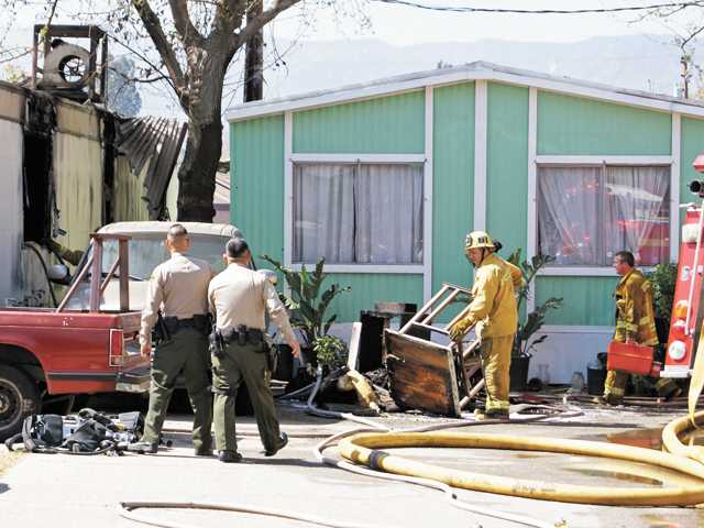 Officials clean up debris after a fire at a mobile home in Newhall on Thursday. A mother and her 6-year-old child suffered minor burns when they tried to get back into the burning home, one firefighter said.
