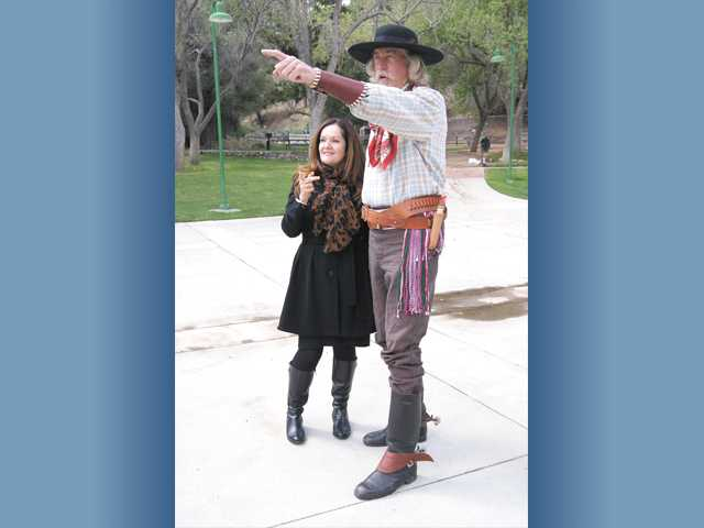 Cowboy-clad John Bertram, a William S. Hart Museum volunteer, points out items of interest for costume conference speaker Theodora Zourkas, of Australia, at the museum in Newhall.