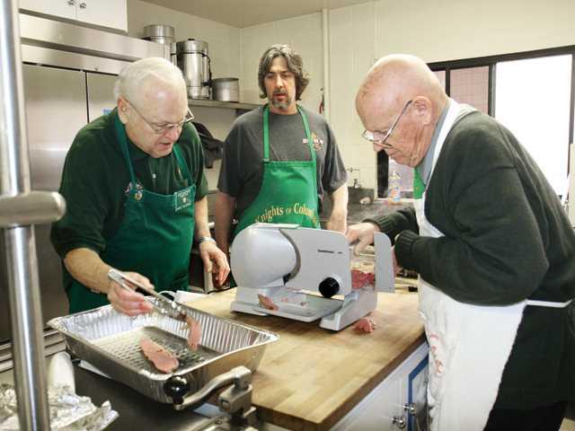 From left, Gundy Tollefson, Steve Bogner and Art Brown slice corned beef.