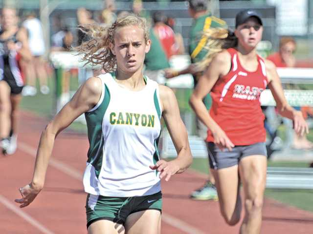 Canyon's Sarah Cipperley, left, stretches out her lead over Hart's Augustina Hansen in the 1,600-meter race during Thursday's meet at Canyon High.