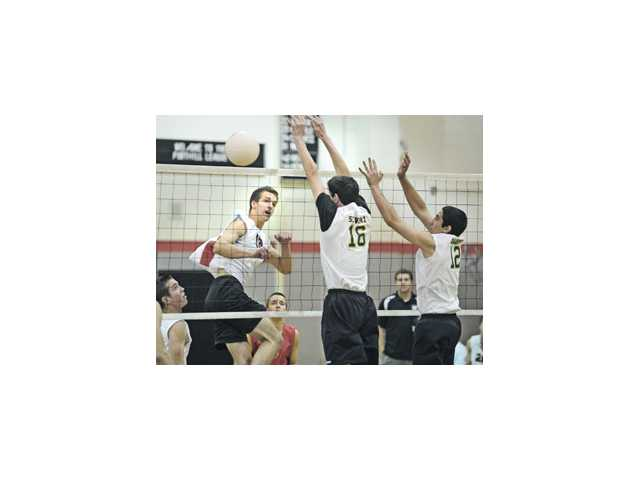 Hart middle blocker Nolyn Preston, center, hits through the block of Canyon defenders Brett Schwarz (16) and Grant Barber (12) on Thursday at Hart High School.