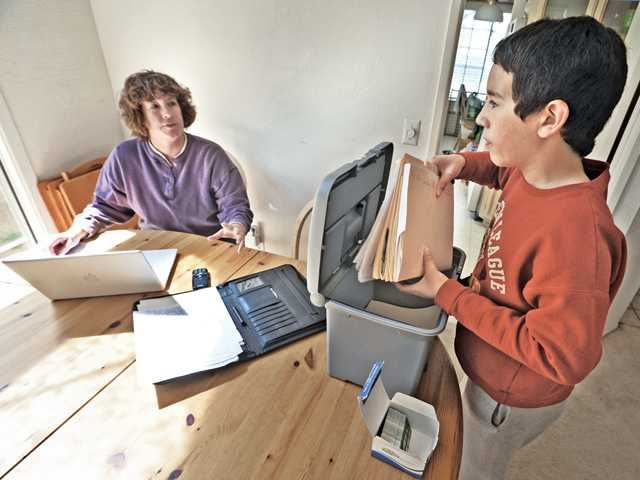 Ryan Harley, 12, helps his mother, Shelly Campbell-Harley, prepare for a meeting in her home office Thursday.