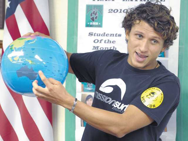 Mision Mexico Program Director Moacir Zeledon points out Australia on a globe as he speaks to a Spanish language class of seventh- and eighth-grade La Mesa Junior High School students on Thursday.