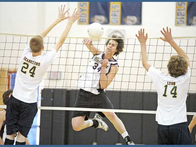 Valencia middle blocker Daniel Salovich puts away a kill as West Ranch's Tanner Skabelund (24) and Christopher Lyon try to block on Tuesday at West Ranch High School. The Vikings fended off the Wildcats 3-1.