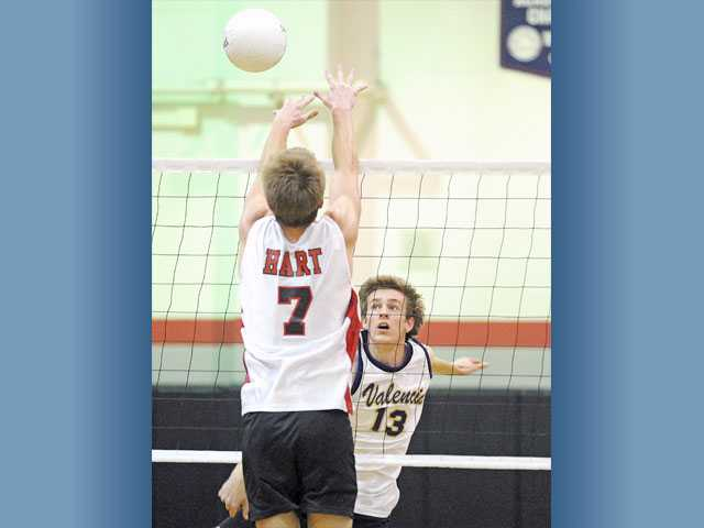 Valencia outside hitter Mark Moss (13) tries to hit past Hart's Jared Turner on Thursday at Hart High.