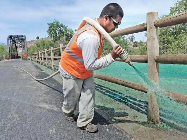 Hydroseed technician Adolfo Hernandez sprays a mix of seed and water on a 7,700-square-foot area around the Iron Horse Trailhead riding and walking path and historic Santa Clara Railroad River Bridge near the intersection of Magic Mountain Parkway and Tourney Road in Santa Clarita on Thursday.