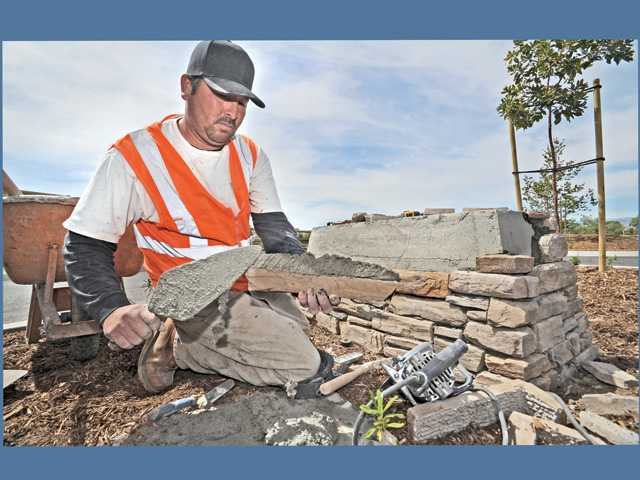 Stone mason Carlos Espericueta installs decorative stones to a sign base at the entrance to the Iron Horse Trailhead riding and walking path and railroad bridge, near the intersection of Magic Mountain Parkway and Tourney Road, on Thursday.