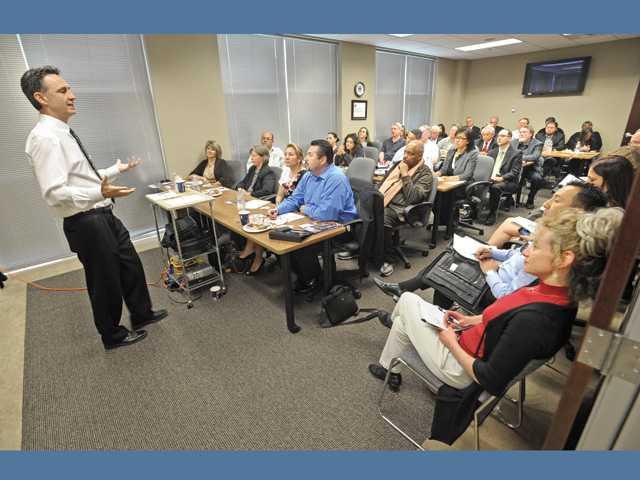 Speaker Tim DiTomaso, left,  speaks to a group about the newly expanded Enterprise Zone at the SCV Chamber of Commerce offices in Santa Clarita on Thursday.