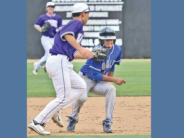 Valencia second baseman Keston Hiura, left, runs down Rocklin High baserunner Stevin Cisneros for the out on Saturday at Valencia high School.