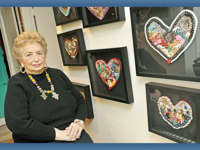 Jaylene Armstrong poses with some of her 11 heart collages in her Newhall home on Wednesday.