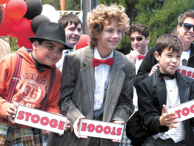 The young Three Stooges, from left: 11-year-old Andrew Cruz as Curly, Henry Bush, 13, as Larry, and 12-year-old Tanner Barnes as Moe, pose for photographers after being named contest winners at the Six Flags Magic Mountain promotional event Sunday.