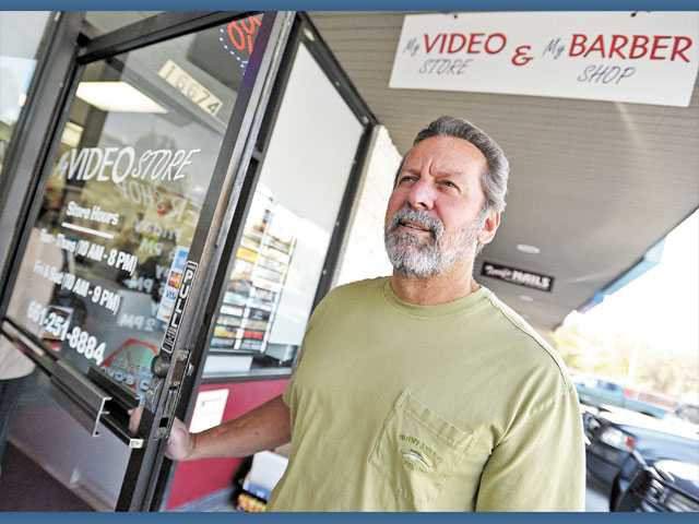 Owner Curt Waite stands outside My Video Store & My Barber Shop at the Sand Canyon Center in Canyon Country on Monday.
