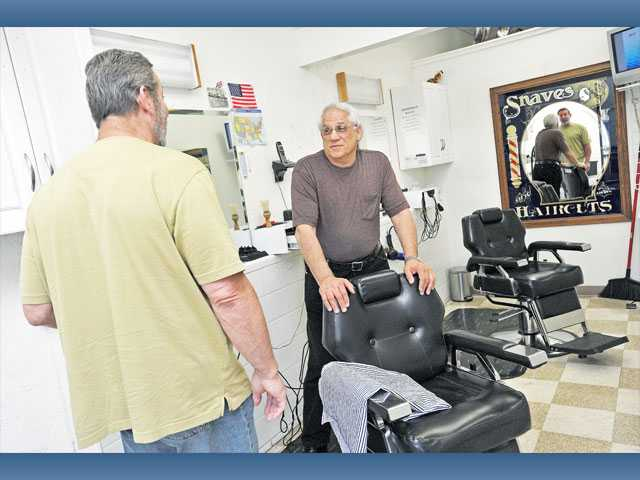 Owner Curt Waite and barber Dominic Ranalo speak inside My Barber Shop in the Sand Canyon Center in Canyon Country on Monday.
