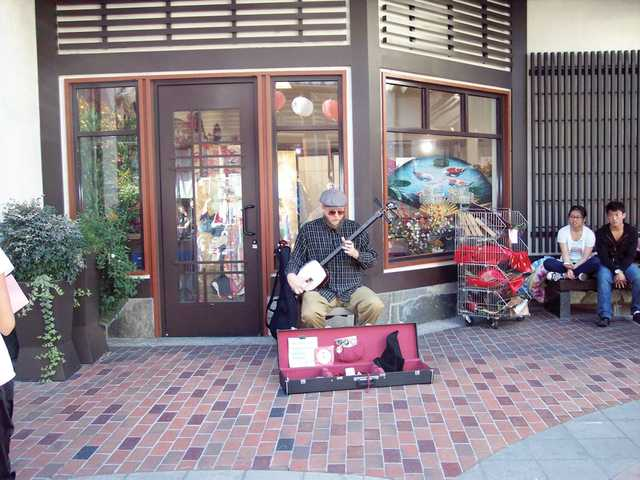 A street musician plays for tips in the courtyard of a shopping center in Little Tokyo.