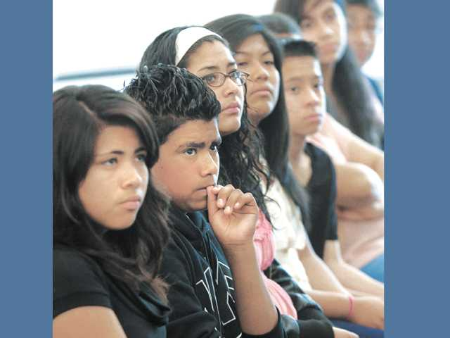 "Jesus Hernandez, 12, second from left, sits with a group from the city of Santa Clarita Activities Center as they listen to Sgt. Leshonda Gill, a member of the ""Tempered Steel"" group speak about her troubled youth and career in the military to a group of local young people at the Santa Clarita Activities Center in Santa Clarita on Wednesday."