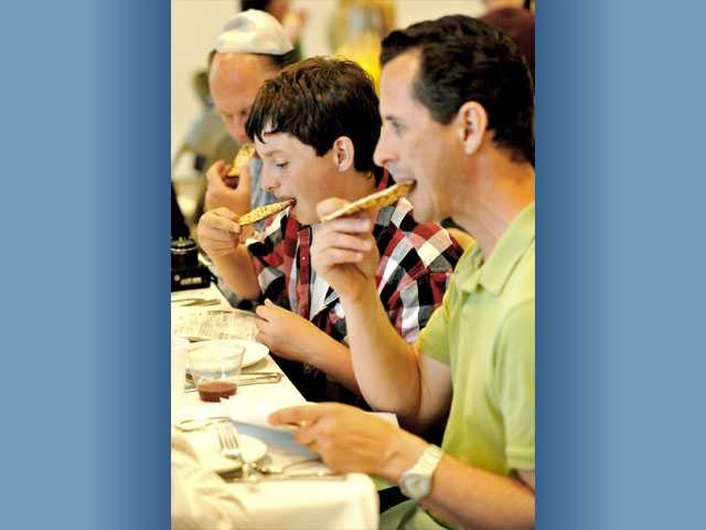 From front, Mark Barton, his son Everett Barton, 13, and Jim Van Winkle eat matzo at the end of the Seder meal as part of the Passover service hosted by Temple Beth Ami at the Valencia Hills clubhouse in Valencia on April 19, 2011.