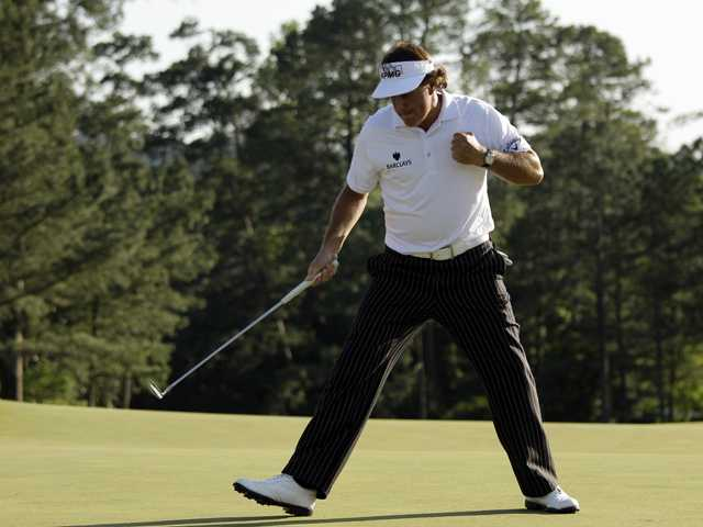 Phil Mickelson pumps his fist after a birdie putt on the 18th green during the third round of the Masters golf tournament Saturday in Augusta, Ga.