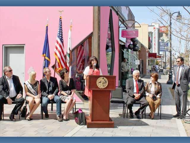 Sassy Couture owner Amanda Marroquin  speaks at a podium as from left, Councilman Marvin Crist; Miss Lancaster Sydney Roth; Vice Mayor Ron Smith; Councilwoman Sandra Johnson; and her parents Hernando Marroquin and Fran Marroquin watch in front of Sassy Couture in Lancaster recently.