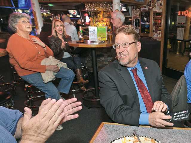 Candidate TimBen Boydston, center, and supporters watch TV screens for preliminary election returns at an election  night party held at Route 66 Classic Grill in Canyon Country.