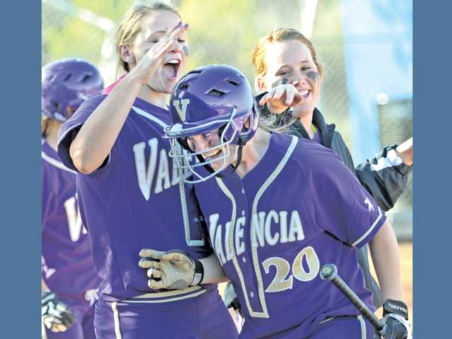 Valencia's Nicole Joseph (20) gets a pat on the helmet from teammates Karlie Habitz, left, and Carly Mortensen after scoring against West Ranch during the sixth inning on Tuesday at West Ranch High School. The Vikings won 4-0.