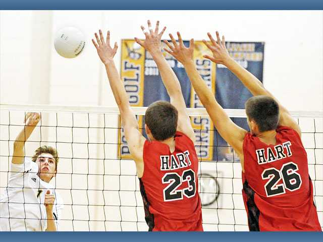 West Ranch outside hitter Dalton Peck, left, hits the ball over the net as Hart's Jordan Shultz (23) and Rhett Almond (26) defend Wednesday at West Ranch High.