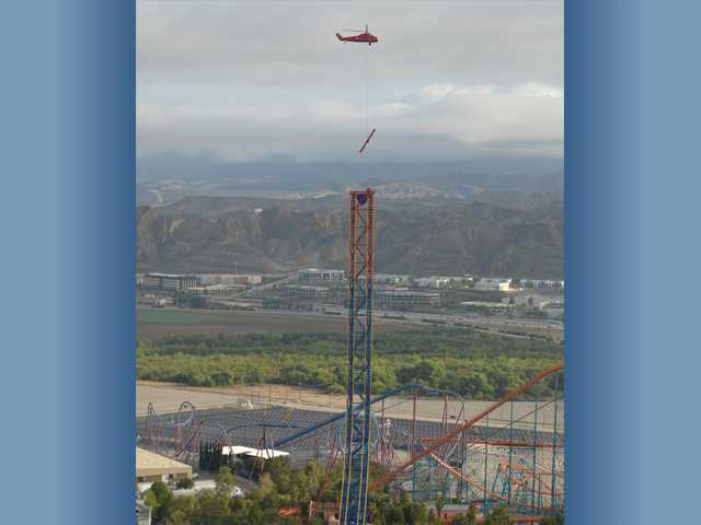 A helicopter lifts crucial pieces of the new Lex Luthor Drop of Doom ride,  which is currently under construction, to the top of the Superman tower at Six Flags Magic Mountain.