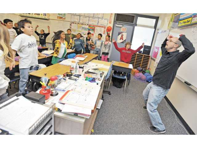 Stepner leads a workout with his combination fourth- and-fifth-grade class between lesson in his classroom.