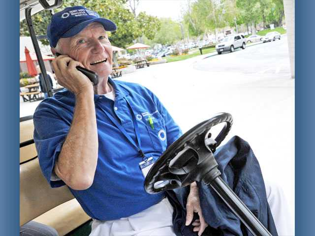 Jim Brush takes a call for service as he volunteers as a shuttle driver.