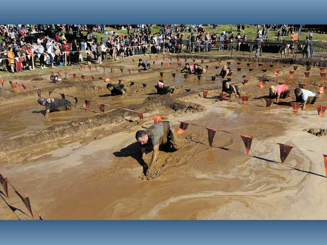 Participants crawl through the mud pit at The Merrell Down & Dirty National Mud and Obstacle Series held at Castaic Lake on Sunday.