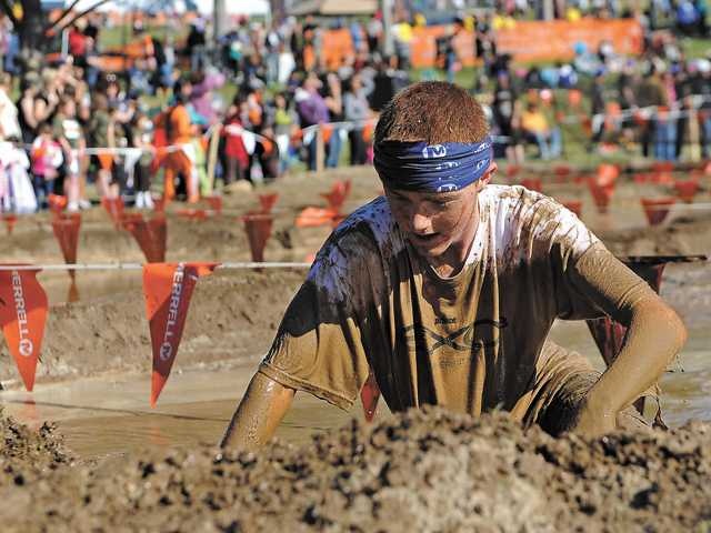 Collin McMenamim, of Stevenson Ranch, crawls out of a mud pit, one of the obstacles in a 10-kilometer race,  in Castaic Lake on Sunday.